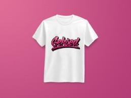 Mise en situation du lettrage Geksed sur un t-shirt blanc uni, seul sur fond rose / magenta