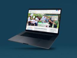 Mise en situation d'un MacBook Pro pris de 3/4, sur fond bleu foncé, avec, dans l'écran, la home page du site internet Paraíso Down