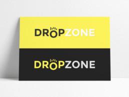 Poster horizontal, posé contre un mur blanc, montrant le logo Dropzone sur 2 fonds de couleur. On y voit le logo sur fond jaune et gris foncé