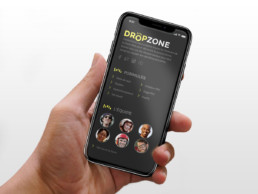 Mise en situation d'un iPhone X tenu par la main gauche d'un homme. On y le footer du site Dropzone en version responsive mobile.