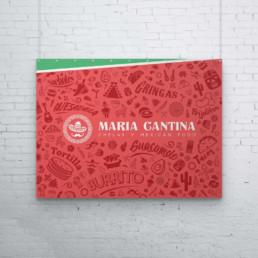 Photo couverture du Maria Cantina : on y voit un poster du logo horizontal de Maria Cantina sur fond rouge avec motifs mexicains autour de ce dernier. Le logo est de couleur blanc et le poster est suspendu sur un mur en brique blanc