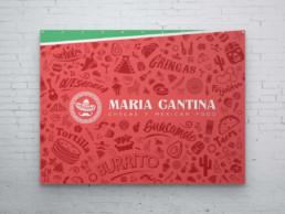 Poster du logo horizontal de Maria Cantina sur fond rouge avec motifs mexicains autour de ce dernier. Le logo est de couleur blanc et le poster est suspendu sur un mur en brique blanc