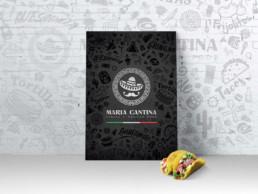 Couverture de la carte menu de Maria Cantina posé verticalement contre un mur de brique blanches : un tacos est posé devant le menu. La couverture menu est de couleur noir avec le logo vertical blanc de Maria Cantina souligné par un liseré vert, blanc, rouge (couleur du drapeau mexicain)